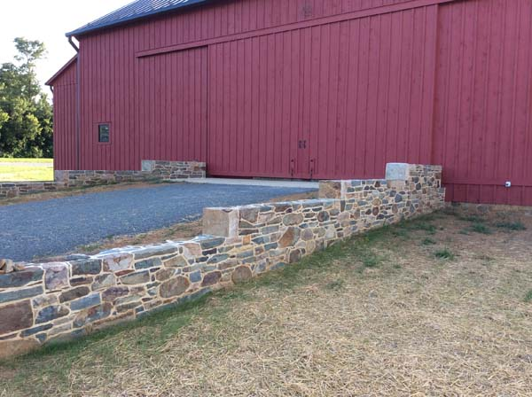 red barn and tiered stone wall